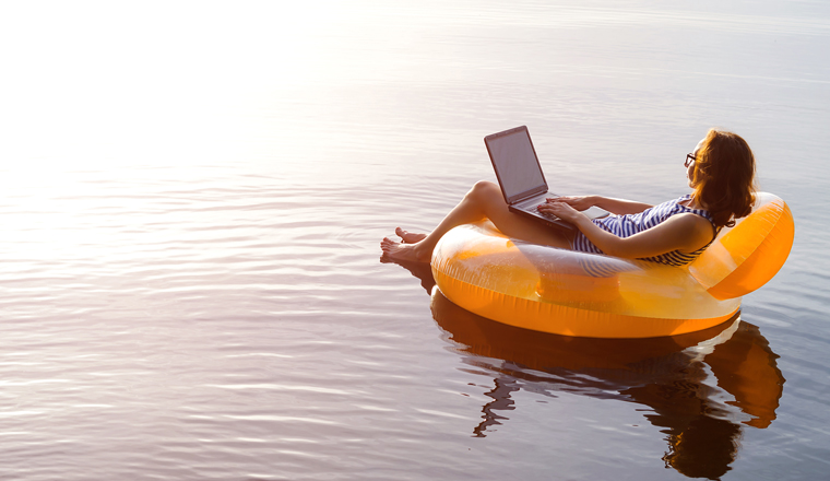 A woman floats on water with an orange inflatable with her laptop