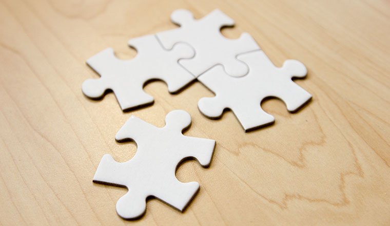 Four white puzzle pieces fit together on a wooden surface