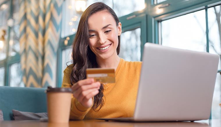 enthusiastic woman reading credit card number while staring down and working on laptop