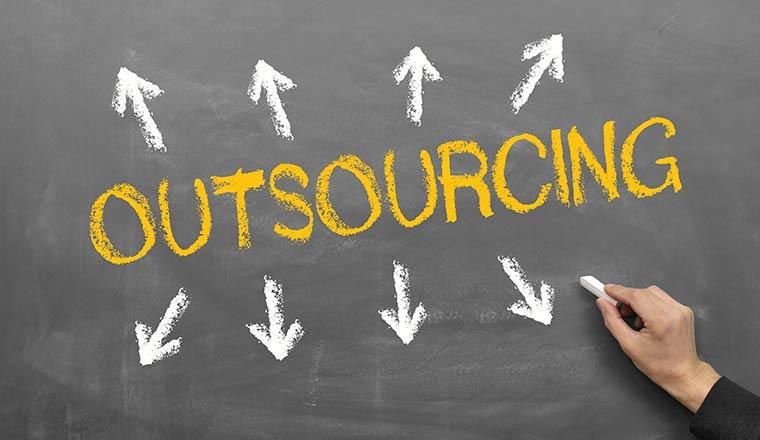 The word outsourcing is written on a blackboard in yellow chalk