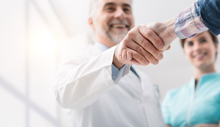 Doctor and female patient meeting at the hospital and shaking hands