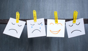 Four post it notes are held by pegs. They have sad, crying, angry and happy faces