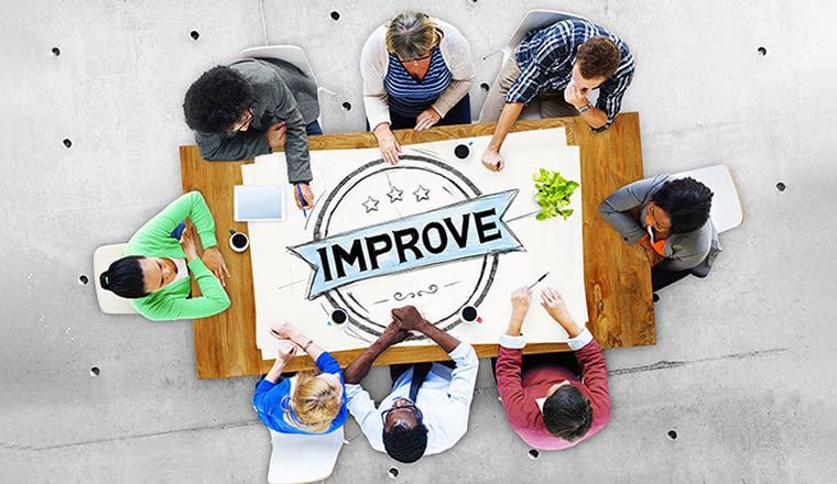 A team sit around a table with improve written on it