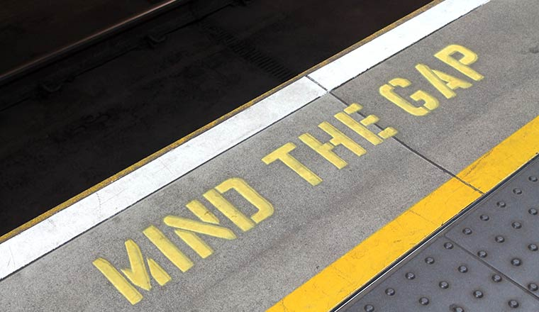 A mind the gap sign painted on the floor of a train station