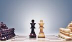 The black and white queen chess piece on a chess board.