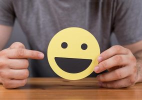 A man holds a smiley face cut out