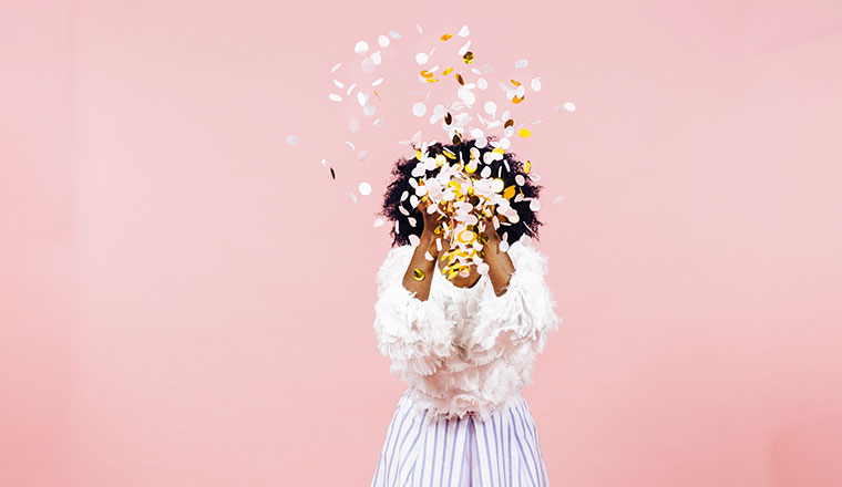 A woman throws confetti into the sky, with a pink background