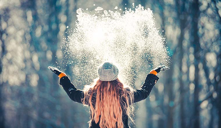 Young woman throwing snow in the air at sunny winter day, back view