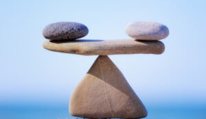 Two zen stones balance on a larger zen stone with a peaceful background
