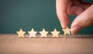 Hand putting wooden five star shape on table. The best excellent business services rating customer experience concept.
