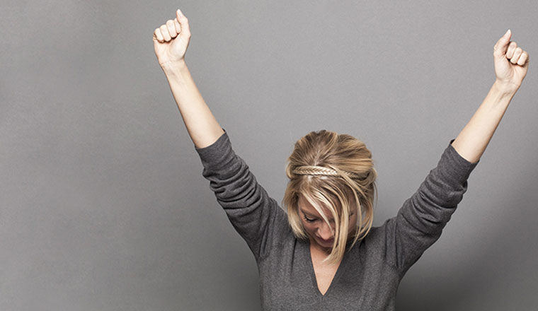 A photo of successful young woman winning with both arms up