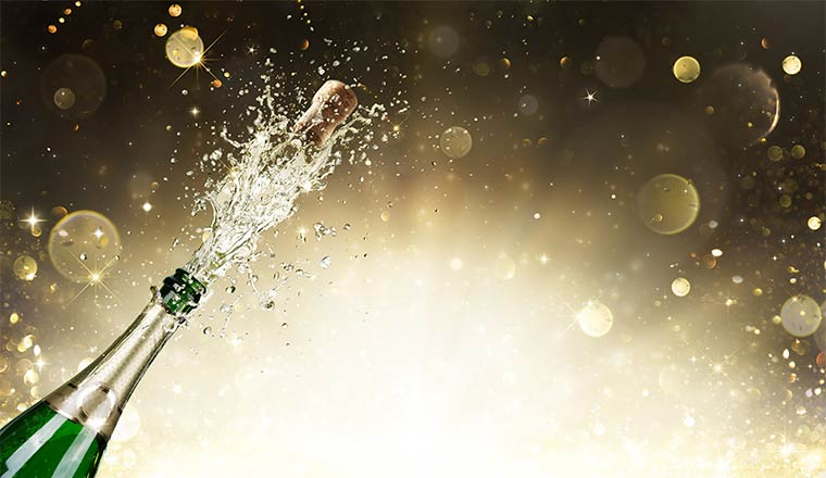 A champagne bottle is uncorked and the champagne flows out