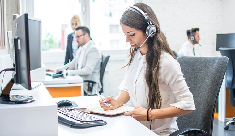 A white woman with long brown hair wears a headset
