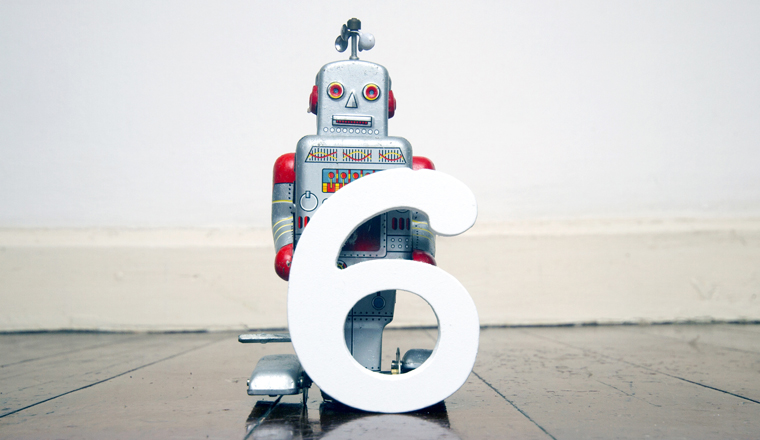 A small robot toy holds the number 6