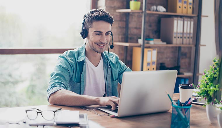 Young smiling experienced operator of call center answering the question of his client