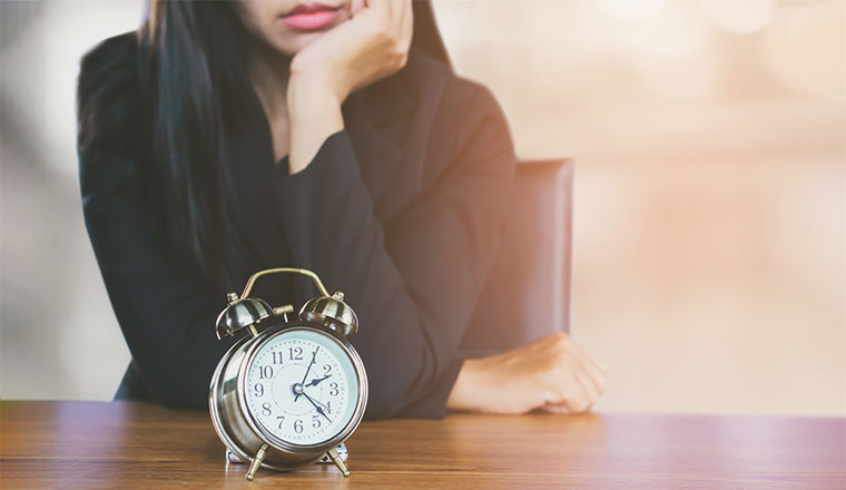A clock is sat on a desk in front of a bored looking lady