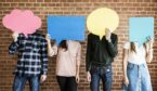A photo of four people holding speech bubbles over their faces