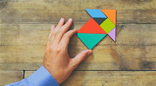 A photo of an arrow made up of puzzel pieces