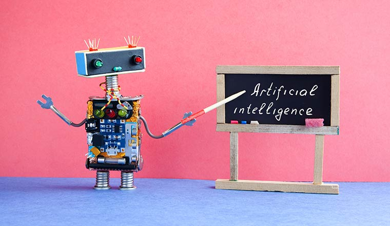 A picture of a robot pointing to chalkboard