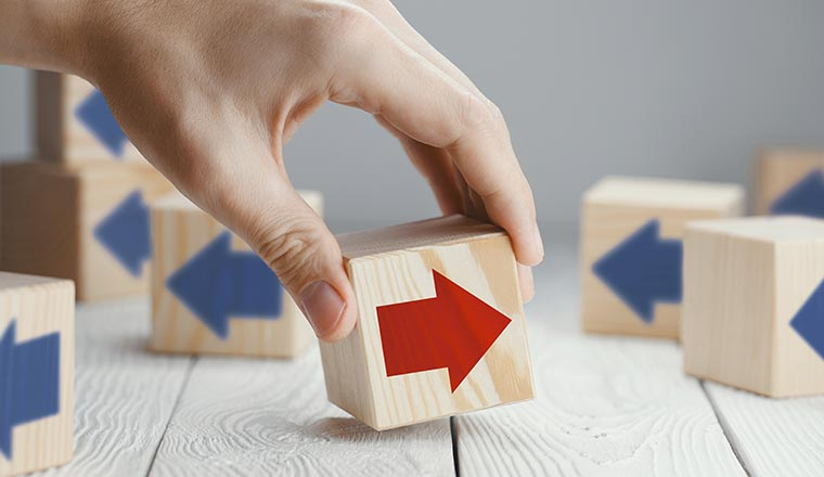 A red arrow on a wooden block faces a different way to blue arrows on other blocks