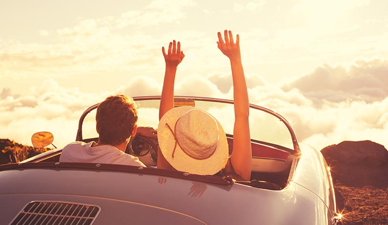 Happy Young Couple Enjoying the Sunset in Classic Vintage Sports Car