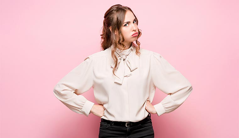 A photo of a frustrated young business woman on pink studio background