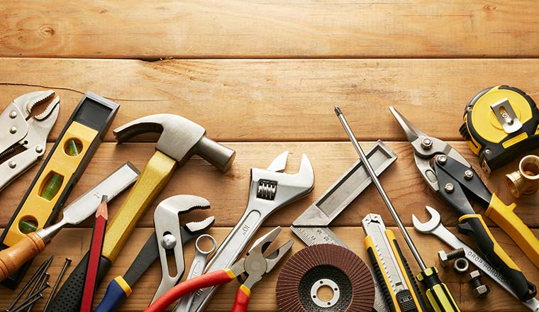 A photo of a variety of tools on wood planks