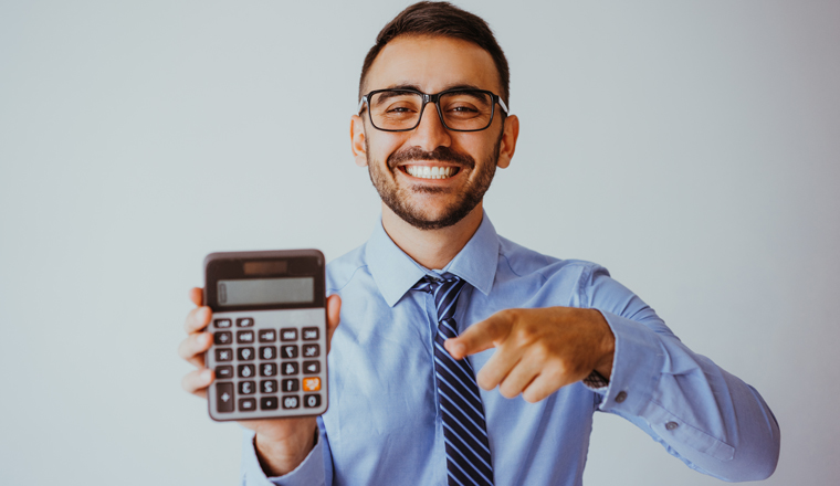 A happy looking man points towards his calculator