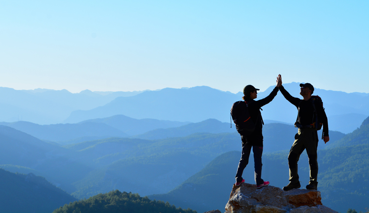 Two people on top of a rock high five