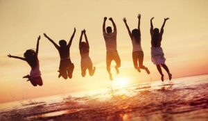 Big group of happy friends having fun and jumps in water against sunset