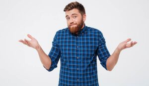 A photo of Confused young bearded man standing and shrugging shoulders