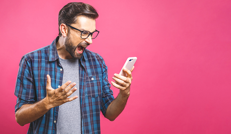 Young caucasian man angry, frustrated and furious with his phone, angry with customer service over pink background.