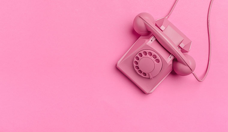 A photo of an old phone against a pink background