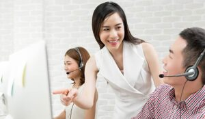 A photo of female Asian supervisor training work with telemarketing customer service agent team in call centre