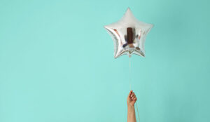 A picture of someone holding a balloon shaped like a star