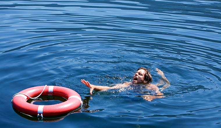 A photo of a man struggling for a life buoy in the water