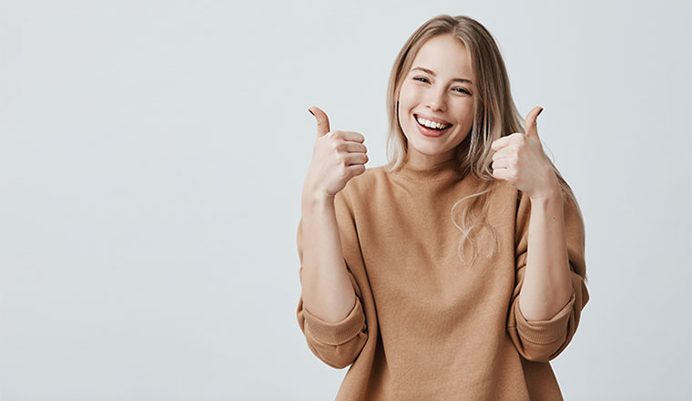 female customer with broad smile, looking at the camera with happy expression, showing thumbs-up with both hands,