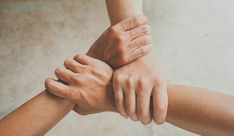A photo of three people joining hands together
