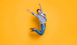 A photo of cheerful man in sneakers, denim outfit, jumping with raised arms