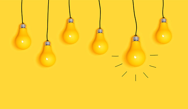 A picture of many hanging light bulbs on a yellow background