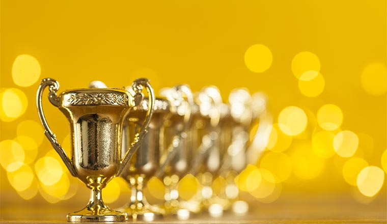 A photo of award trophies against bright yellow background with blurred lights