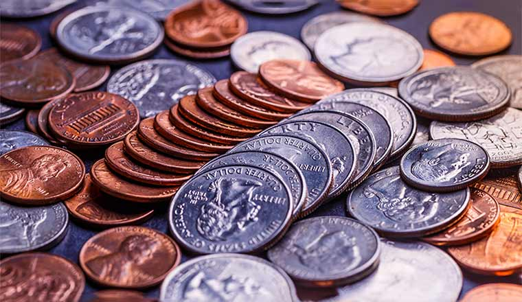 A photo of American coins and us dollars on a black table