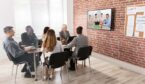 A photo of a group of business people having video conference in boardroom
