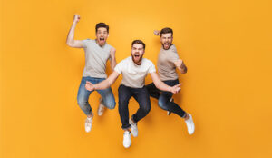A photo of three happy men jumping together