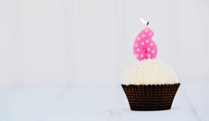 A photo of a cupcake with a candle shaped like a six