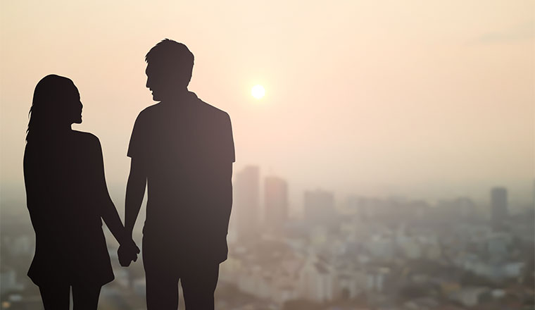A photo of two silhouettes holding hands