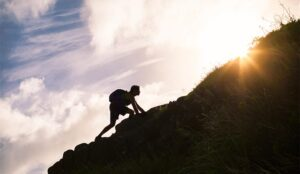 A picture of a person climbing up a hill