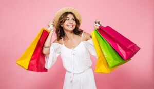 A photo of a joyful smiling girl holding lots of colorful shopping bags and looking away isolated over pink background