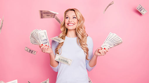 A photo of a woman standing under a shower of money