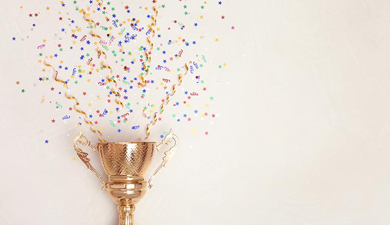 A photo of a trophy with confetti coming from the top